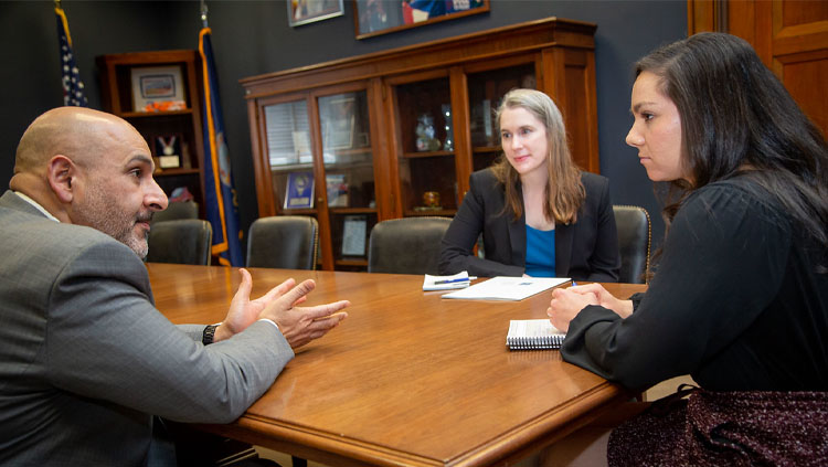Three people sit around a table discussing science advocacy.