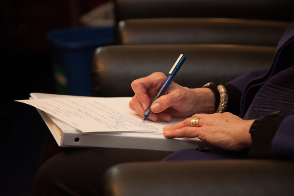 Image of a person taking notes at a legislative meeting.