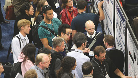 A man explaining his poster presentation on the poster floor as several other people gather round listening to the presentation