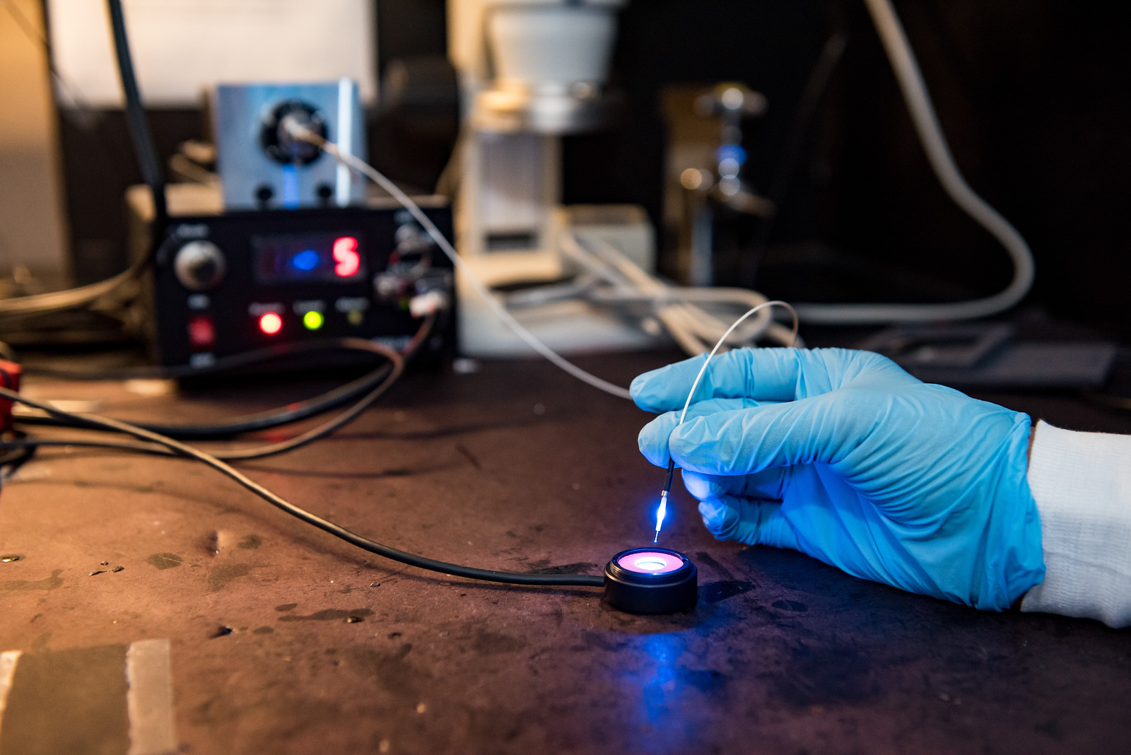 a gloved hand working with a lighted piece of scientific equipment