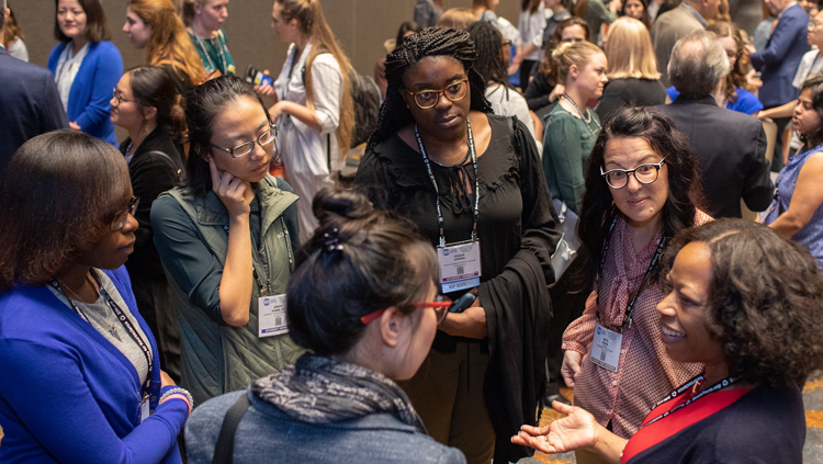 Six women conversing in a circle at the Annual Meeting