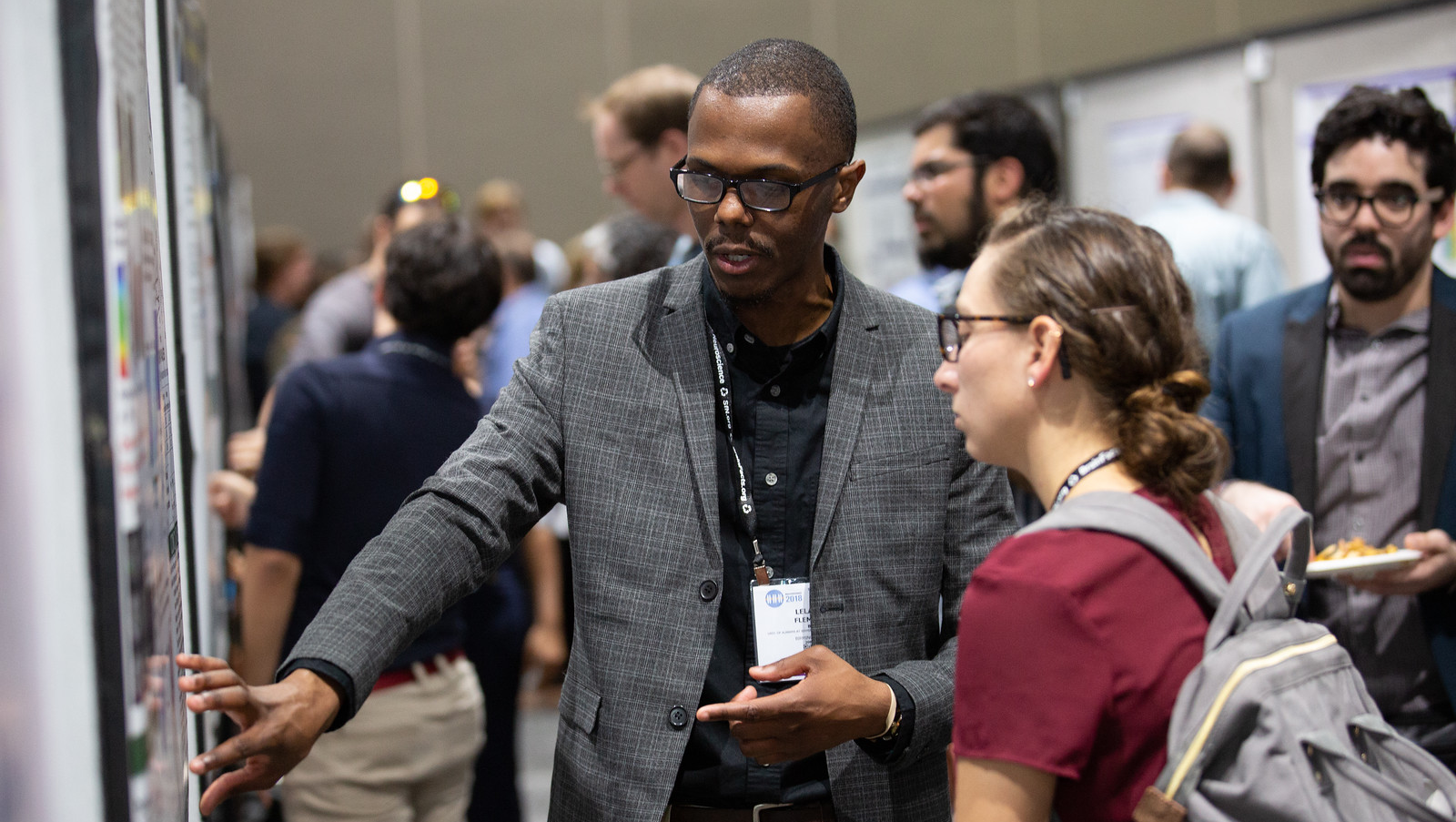 Poster Presenter explaining his work to another attendee at Neuroscience 2018
